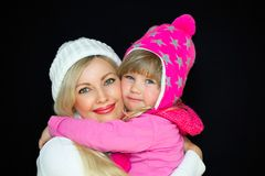 Mom and daughter embrace, in knitted hats, on a black background. Happy family, smiles and joy. Studio photography royalty free stock photos