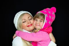 Mom and daughter embrace, in knitted hats, on a black background. Happy family, smiles and joy. Studio photography royalty free stock photo