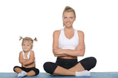 Mom and daughter engage in fitness on mat Royalty Free Stock Images