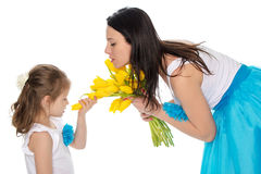 Mom and daughter enjoying the fragrance of flowers. Stock Photo