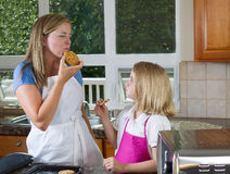 Mom and daughter enjoying freshly baked cookies in the Kitchen Stock Photos