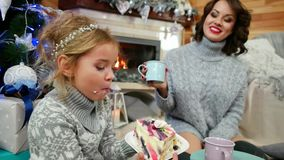Mom and daughter enjoying spending time together, girl with pleasure eating a large piece of cake at The Christmas tree stock video footage