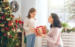 Mom and daughter exchanging gifts stock image