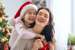 Mom and daughter exchanging gifts stock images