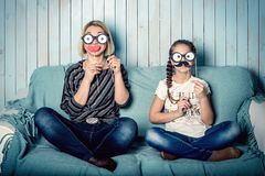 Mom and daughter with false mustaches. Funny mom and daughter with false mustaches, playing at home Royalty Free Stock Image