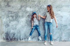 Mom with daughter in family look. Young beautiful mom with her daughter wearing blank gray t-shirt and jeans posing against rough concgrete wall, minimalist Royalty Free Stock Photo