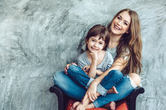 Mom with daughter in family look. Young beautiful mom with her daughter wearing blank gray t-shirt and jeans posing against rough concgrete wall, minimalist Stock Photo