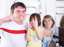 Mom, daughter and father brush their teeth Royalty Free Stock Photography