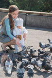 Mom and daughter feeding pigeons Royalty Free Stock Images