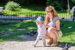 Mom and daughter feeding pigeons in a park on the lake Royalty Free Stock Images