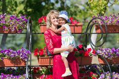 Mom and daughter at a flower bed. stock images