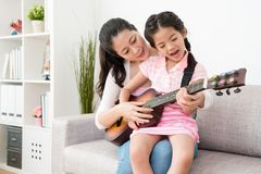 Mom and daughter focus on the guitar. Royalty Free Stock Images