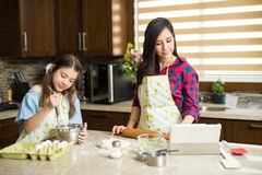 Mom and daughter following recipe. Cute girl and her mother cooking in the kitchen and following an online recipe on a tablet Royalty Free Stock Photography