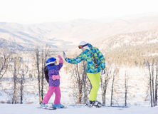 Mom and daughter give high five while snow skiing royalty free stock images