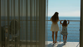 Mom and daughter go to the balcony with the sea view from the guest room Royalty Free Stock Photo