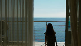 Mom and daughter go to the balcony with the sea view from the guest room Stock Photo