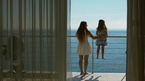 Mom and daughter go to the balcony with the sea view from the guest room Royalty Free Stock Photos