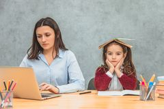 Mom and daughter on a gray background. During this, the girl put an open book on the book and rejoices. Mom quietly works on a computer royalty free stock images