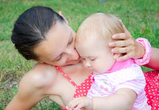 Mom and daughter on the green grass. Mom gently embraces her daughter in the park on the green grass royalty free stock photo