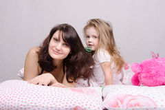 Mom and daughter with a hairbrush in her bed Royalty Free Stock Photos