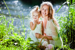 Mom and daughter happy smile on the background of the forest and. Water in backlight Royalty Free Stock Photos