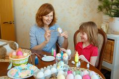 Mom and daughter have fun painting eggs for Easter stock images