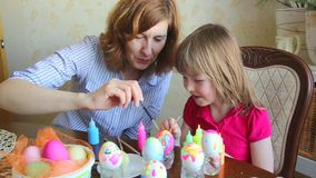 Mom and daughter have fun painting eggs for Easter stock footage