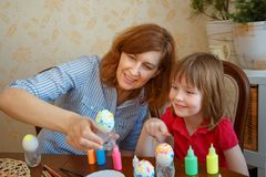 Mom and daughter have fun painting eggs for Easter royalty free stock images