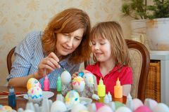 Mom and daughter have fun painting eggs for Easter stock image