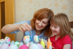 Mom and daughter have fun painting eggs for Easter stock photos