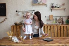 Mom and daughter have fun playing together with tablet in home i Royalty Free Stock Photography
