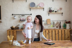 Mom and daughter have fun playing together with tablet in home i Stock Photos