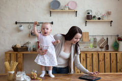 Mom and daughter have fun playing together with tablet in home i Stock Image