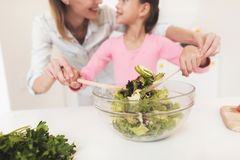 Mom and daughter have fun while preparing a salad. They are in a bright kitchen. A mother is teaching her daughter to prepare a salad Stock Photo