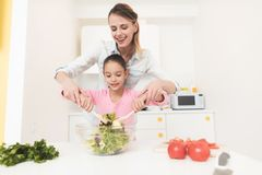 Mom and daughter have fun while preparing a salad. They are in a bright kitchen. A mother is teaching her daughter to prepare a salad stock images