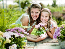 Mom and daughter have fun in the work of gardening. In a greenhouse Stock Photography