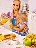 Mom and daughter having breakfast in the kitchen. Stock Image