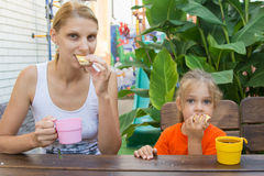 Mom and daughter having breakfast with tea and sandwiches sitting on the veranda Royalty Free Stock Photos