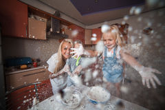 Mom and daughter having fun with flour. Girl throws flour on a camera royalty free stock image