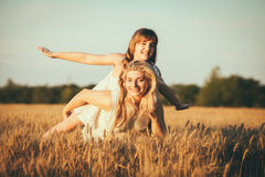 Mom and daughter having fun by the lake, field outdoors enjoying nature Stock Photos