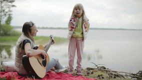 Mom and daughter having fun outdoors by the lake. stock footage