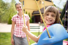 Mom and daughter having fun on playground Stock Image