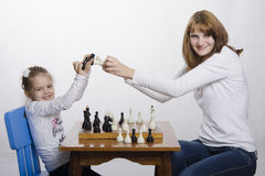 Mom and daughter having fun playing chess Royalty Free Stock Images