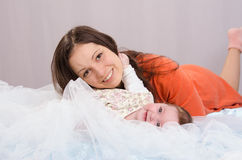 Mom and daughter having fun six-month lay on bed. Mom and daughter on the couch six-month royalty free stock photography