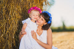 Mom and daughter on a haystack joyful summer day Stock Images