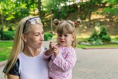 Mom with daughter in her arms in a beautiful park. stock photo
