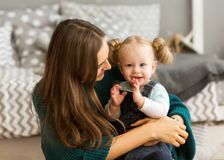 Mom with daughter on her arms emotionally hugs her at home. Mothers Day Royalty Free Stock Photos