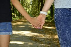 Mom and daughter hold hands stock image