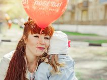 Mom and daughter holding a balloon. In the Park royalty free stock photos