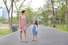 Mom and daughter holding hands in the outdoor nature garden royalty free stock photo